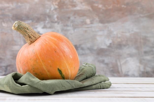 Una zucca arancione matura si trova su un tovagliolo verde. rustico. copia spazio