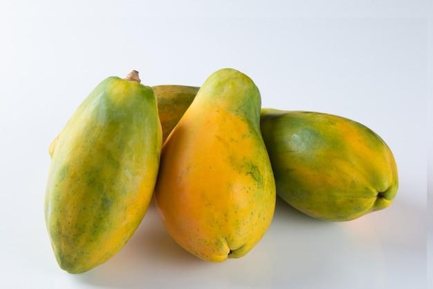 Frutta matura della papaia su superficie bianca.