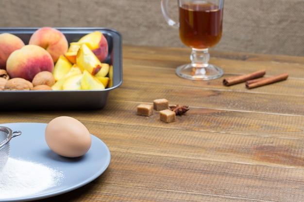 Pesche e noci mature in vassoio di metallo. farina, setaccio e uovo su lastra grigia. copia spazio. fondo in legno.