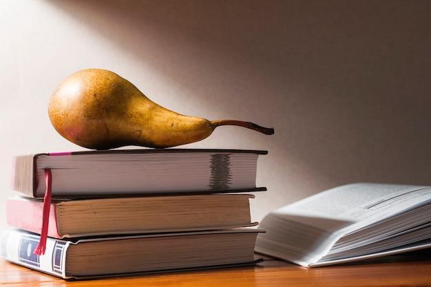 Una pera matura giace su tre libri. accanto c'è un libro aperto.