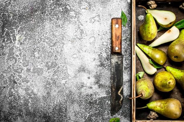 Pere mature su un vassoio con un vecchio coltello. su fondo rustico.