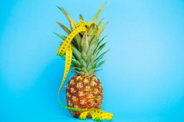 Ananas maturo con misura di nastro sul blu