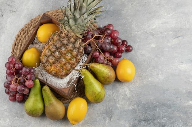 Ananas maturo in una scatola di legno con vari frutti freschi sulla superficie in marmo.