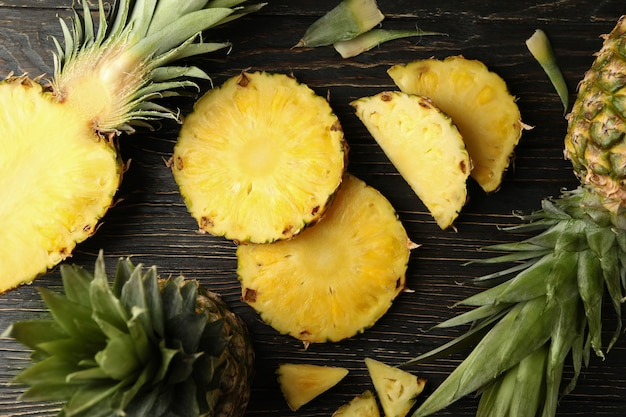 Ananas maturo e fette su fondo di legno, vista dall'alto