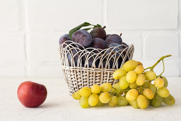Prugne mature in un cesto di vimini, una mela e un grappolo di uva verde matura su sfondo di mattoni bianchi