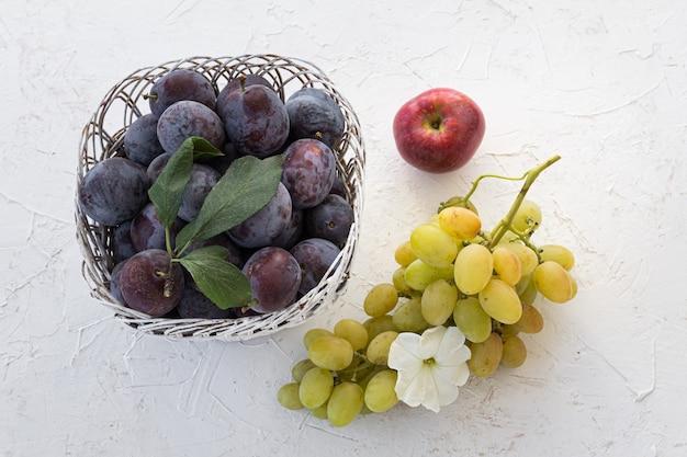 Prugne mature in un canestro di vimini una mela e un grappolo di uva verde matura su fondo bianco strutturato