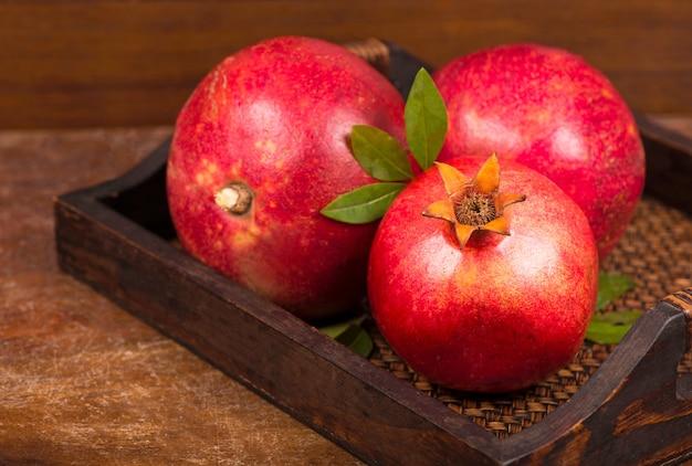 Frutti maturi del melograno sullo sfondo di legno. vista dall'alto.