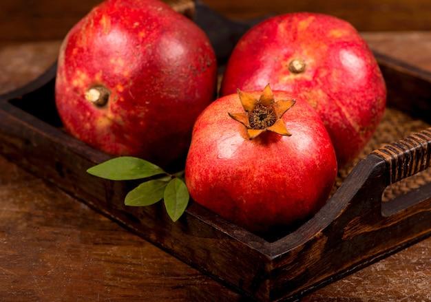 Frutti maturi del melograno sui precedenti di legno. vista dall'alto.