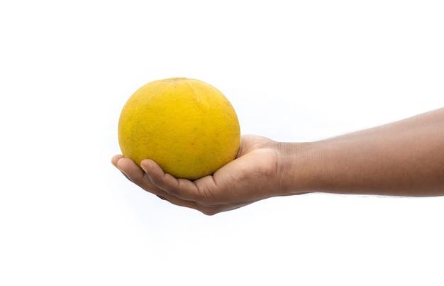 Frutta matura del pomelo su una mano maschio isolata su fondo bianco