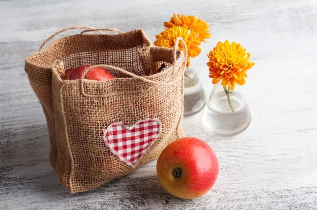 Mele rosse mature e borsa con cuore sulla tavola rustica. cibo crudo autunnale