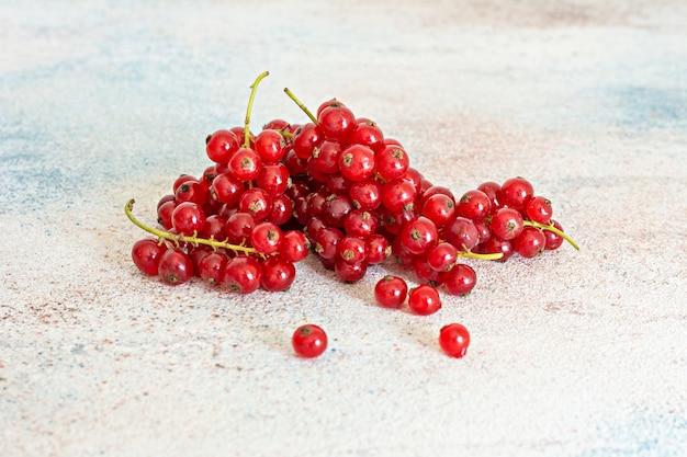 Ribes rosso maturo su sfondo chiaro. frutti di bosco freschi estivi, vitamine sane.