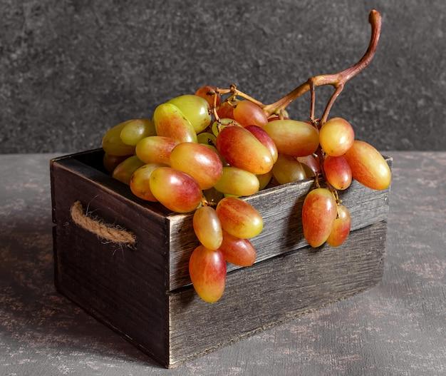 Uva rossa matura in una scatola di legno su uno sfondo grigio scuro