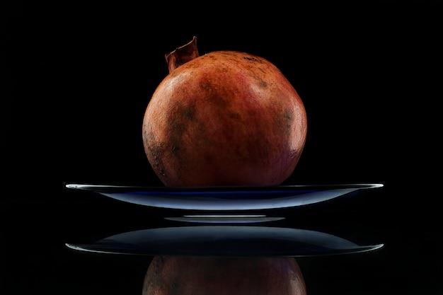 Melograno rosso maturo in un piatto blu su un tavolo di vetro.