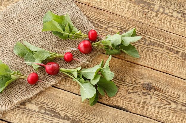 Ravanelli rossi maturi con gambi verdi su tela di sacco e vecchie tavole di legno. vista dall'alto. raccolta primaverile di ortaggi in un giardino.