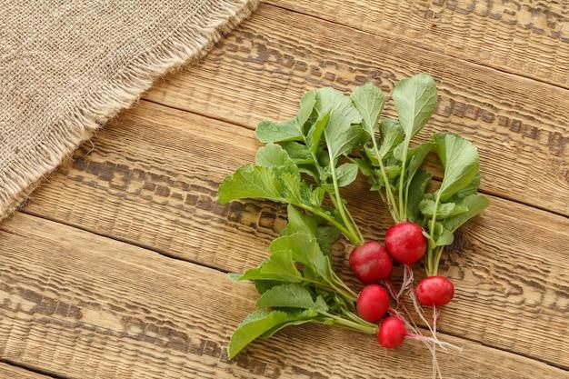 Ravanelli rossi maturi con gambi verdi con tela di sacco su vecchie tavole di legno. vista dall'alto. raccolta primaverile di ortaggi in un giardino.