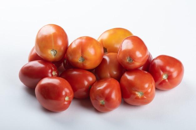 Pomodoro rosso maturo impilato nella tabella bianca.