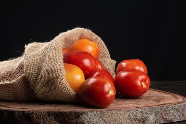 Pomodoro rosso maturo su legno con tavola nera.