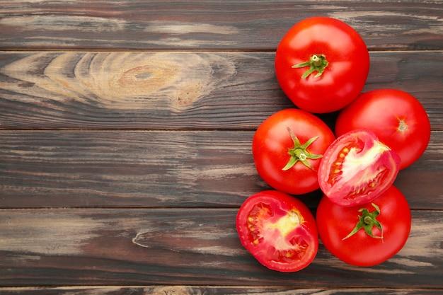 Pomodori rossi maturi su un fondo di legno marrone.