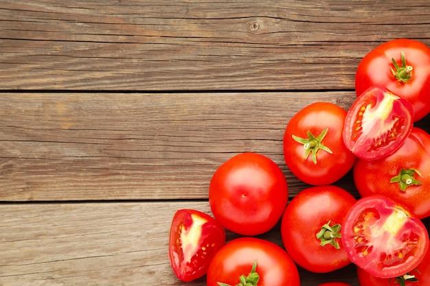 Pomodori rossi maturi su un fondo di legno grigio.