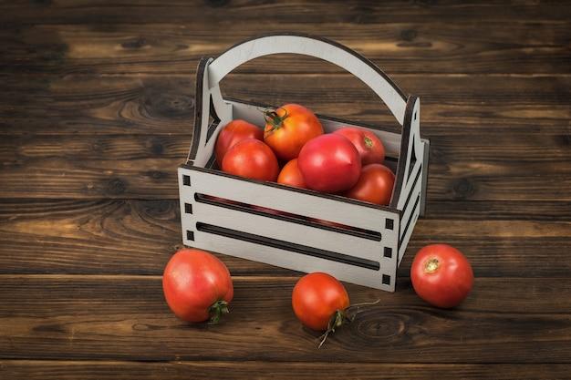 Pomodori rossi maturi in una scatola di legno su un tavolo di legno.