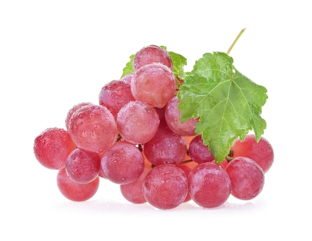 Uva bagnata rossa matura con le gocce. mazzo rosa con foglie isolate su bianco.