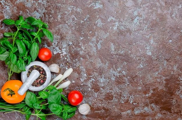 Pomodori rossi e gialli maturi, cipolla verde e basilico, aglio, sale e spezie su uno sfondo di pietra scura. vista dall'alto, spazio di copia.