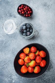 Fragola matura, mirtillo rosso e mirtillo in una ciotola e vaso, laici piatta Foto Premium