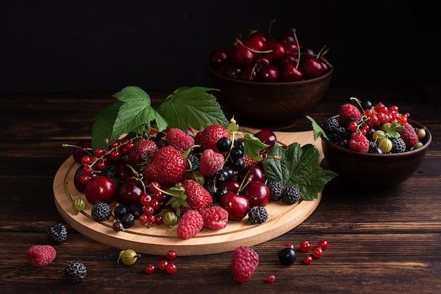 Bacche estive mature, fragole, ciliegie, ribes, lamponi su un vassoio di legno su uno sfondo scuro, cibo vegetariano sano, primo piano.