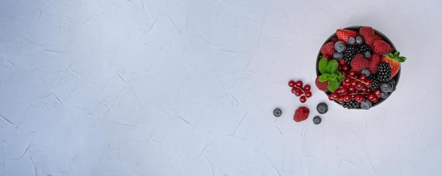 Bacche differenti dolci mature in ciotola sulla tavola di legno. concetto di raccolto. bacche fresche.