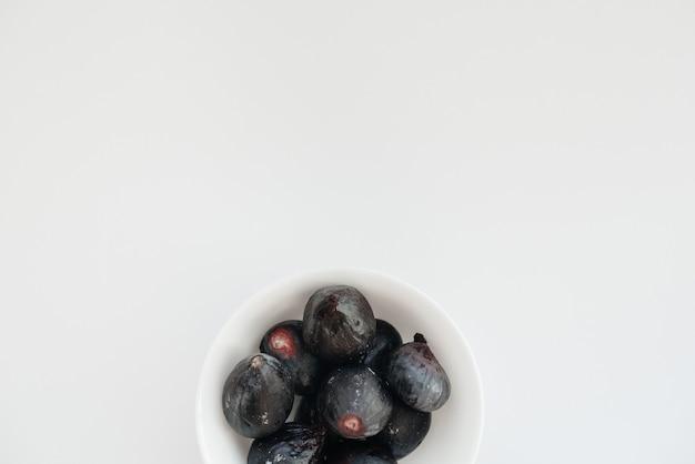 Fichi maturi e dolci tagliati e disposti in un piatto su una superficie bianca