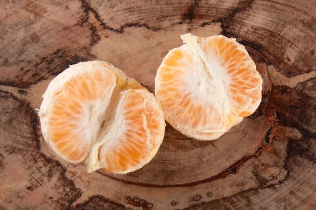 Frutta matura del mandarino sbucciata e aperta su fondo di legno rustico.