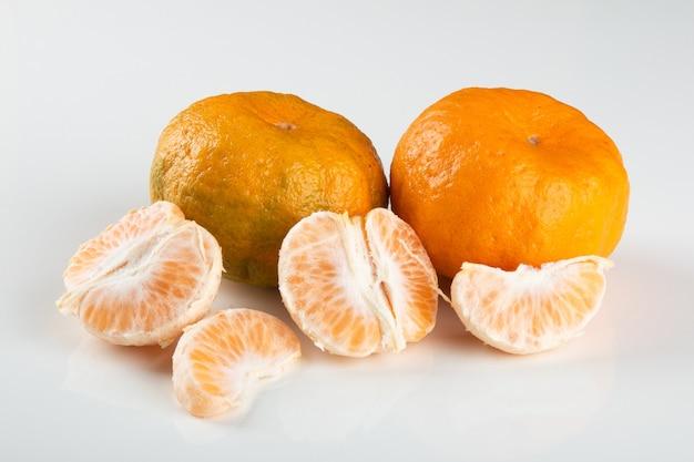 Frutta matura del mandarino con i pezzi su fondo bianco.