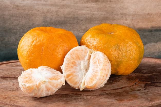 Frutta matura del mandarino con i pezzi su fondo di legno.