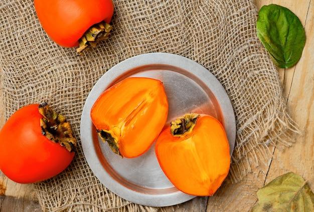 Frutti maturi gustosi cachi arancio, vista dall'alto. metà di cachi freschi su una piastra metallica e bacche di cachi intere su una stuoia di stuoia, layout. tavolo rustico in legno