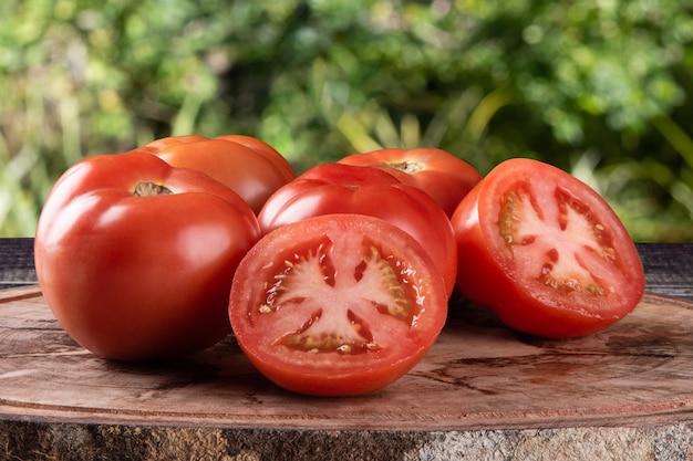 Pomodori maturi tagliati su legno con superficie verde sfocata.