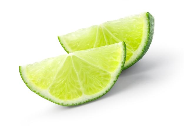 Spicchi maturi di lime verde isolati su sfondo bianco