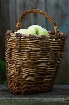 Mele bianche mature che versano in un cesto di vimini in giardino. nuovo raccolto. vitamine e cibo sano. verticale.