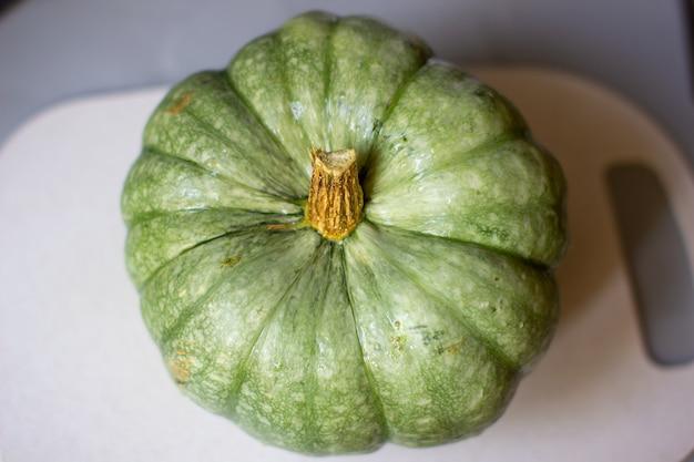 Zucca verde matura e intera in autunno sul tagliere in cucina.