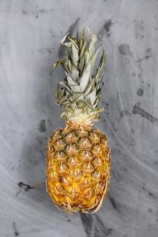 Ananas maturo intero su sfondo grigio cemento.