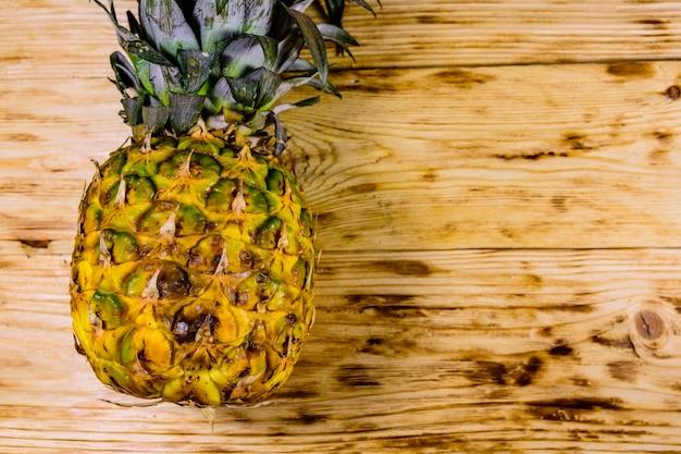 Intero ananas maturo sulla tavola di legno rustica. vista dall'alto