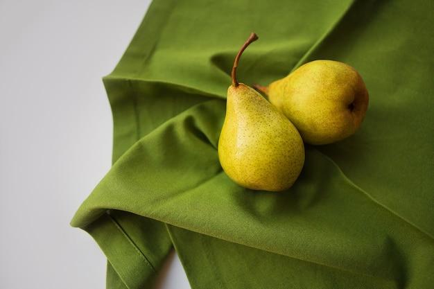 Una pera gialla matura giace su un panno verde