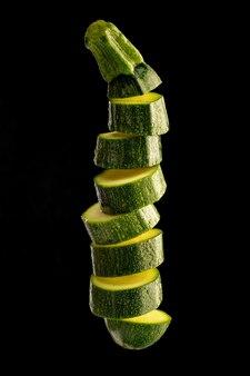 Zucchine mature tagliate a fette e lanciate in aria isolata sul nero