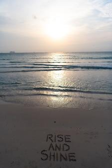 Alzati e risplendi. mattina presto, alba sul mare. tramonto sull'oceano sull'acqua di mare con il cielo al tramonto. parole sulla sabbia della spiaggia. alba dorata di vista sul mare sopra il mare. bellissimo concetto di natura. spiaggia di miami.