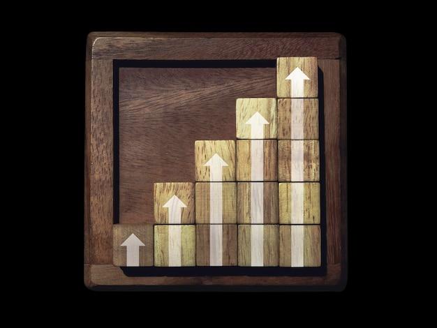 Frecce in aumento su blocchi di legno grafici con passaggi su telaio in legno isolato su sfondo nero, processo di crescita aziendale e concetto di miglioramento economico.