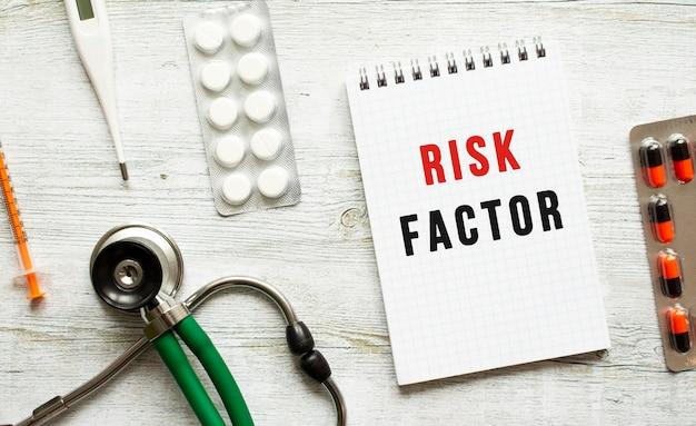 Fattore di rischio è scritto in un taccuino su un tavolo bianco accanto a pillole e uno stetoscopio. concetto medico