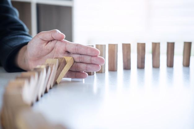 Rischio e strategia nel mondo degli affari, immagine della mano che interrompe la caduta crollo del blocco in legno effetto domino da blocco rovesciato continuo, prevenzione e sviluppo alla stabilità