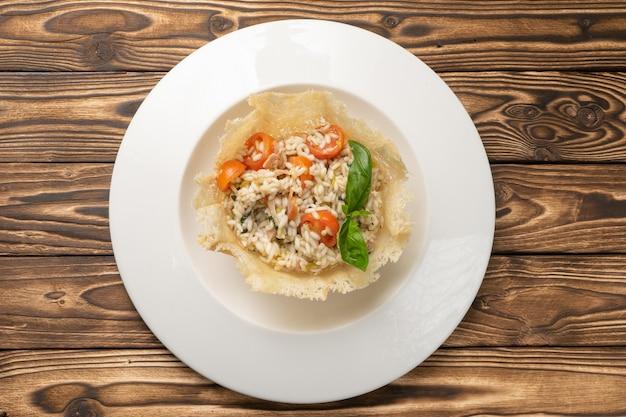 Risotto con pancetta, pomodorini e basilico in un piatto di ceramica bianca