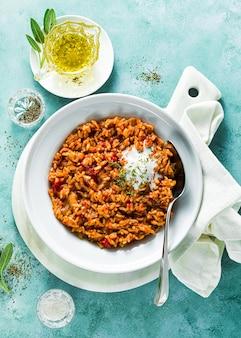 Risotto con cipolle caramellate, pomodori e crema di cocco su un piatto sul tavolo. mix di cucina asiatica e mediterranea