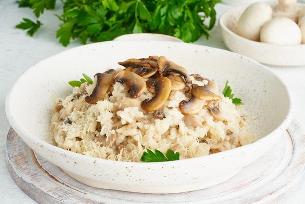Risotto ai funghi nel piatto. porridge di riso con funghi e prezzemolo