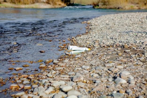 Inquinamento del fiume vicino alla riva, immondizia vicino al fiume, rifiuti alimentari di plastica, che contribuiscono all'inquinamento.